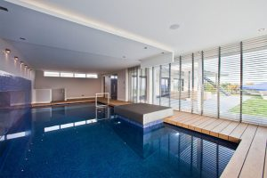 indoor-pool-modern-home-design-with-blue-mosaic-ceramic-tile-and-deck-with-wooden-floor-planks-plus-white-window-blinds